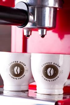 Dwie filiżanki porannej czarnej kawy na czerwonym ekspresie do kawy. makieta do swojego projektu,