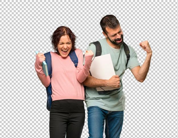 Dwóch studentów z plecakami i książkami świętujących zwycięstwo i cieszących się z wygranej