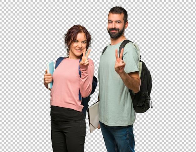 Dwóch uczniów z plecakami i książkami szczęśliwych i liczących dwóch palcami