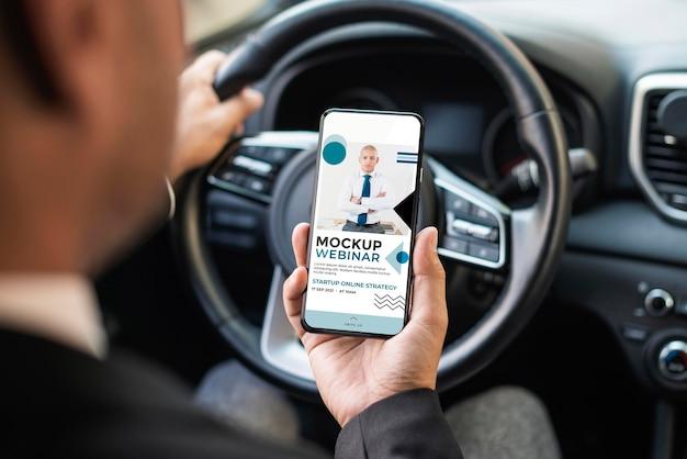 Działalności człowieka w samochodzie z makietą telefonu