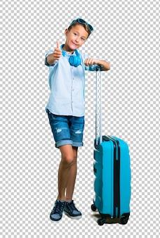 Dziecko z okularami przeciwsłonecznymi i hełmofonami podróżuje z jego walizką daje aprobata gestowi