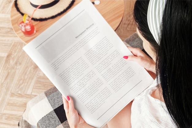 Dziewczyna na kanapie czyta makietę gazety