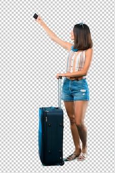 Dziewczyna podróżuje z jej walizką bierze selfie z wiszącą ozdobą