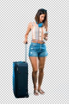 Dziewczyna podróżuje z walizką, wysyłając wiadomość lub e-mail z telefonu komórkowego