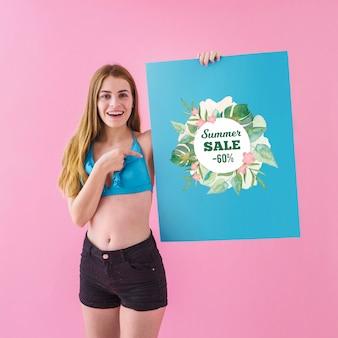 Dziewczyna pokazuje plakat sprzedaż lato