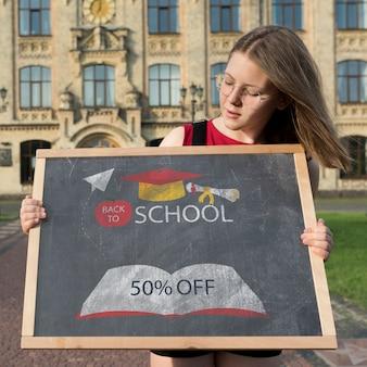 Dziewczyna trzyma blackboard egzamin próbnego z szkłami