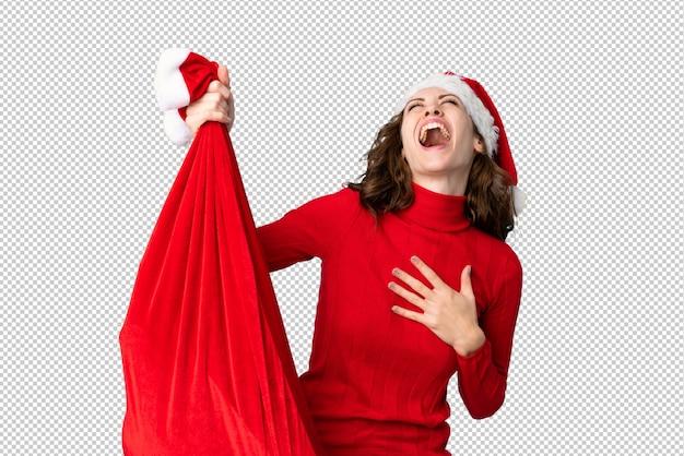 Dziewczyna w kapeluszu boże narodzenie trzyma worek pełen prezentów