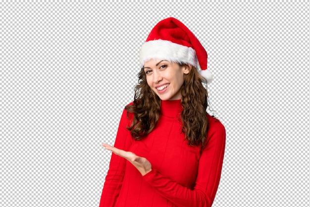 Dziewczyna z czapką świąteczną rozkłada ręce na bok, zapraszając do siebie