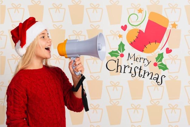 Dziewczyna z santa kapeluszem używać megafon
