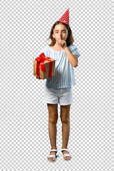 Dziewczynka na przyjęcie urodzinowe trzyma prezent wyświetlono znak zamknięcia gest usta i ciszy