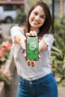 Dziewczyny mienia smartphone mockup z ogrodnictwa pojęciem