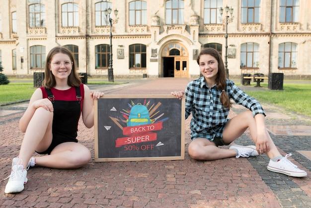 Dziewczyny siedzi podczas gdy trzymający blackboard makietę
