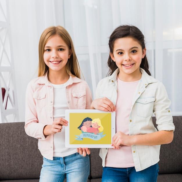 Dziewczyny stojące i trzymające makietę tabletu