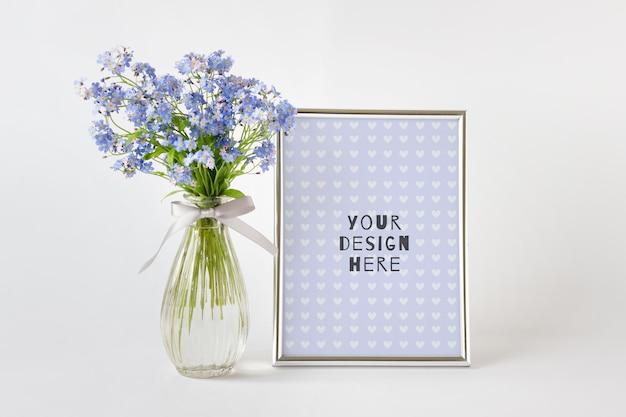 Edytowalna makieta psd z metaliczną srebrną ramką a4 i niebieskimi letnimi kwiatami na białym tle