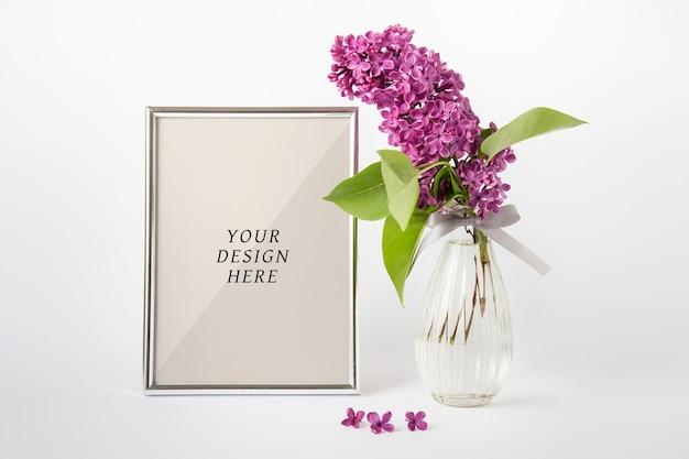 Edytowalna makieta psd z pustą srebrną ramką a4 i fioletową gałązką bzu w szklanym wazonie