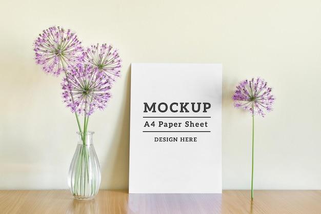 Edytowalna makieta psd ze stojącym arkuszem papieru a4 i fioletowymi letnimi kwiatami na drewnianej powierzchni