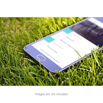 Ekran telefonu komórkowego na trawie makijaż