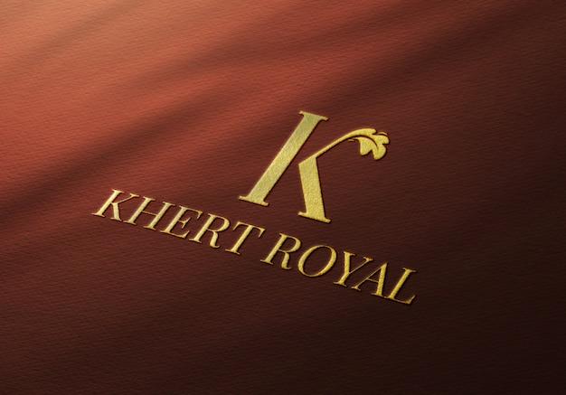 Elegancka makieta ze złotym logo na czerwonym materiale
