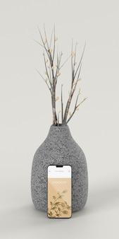 Elegancki asortyment z makietą smartfona i wazonem