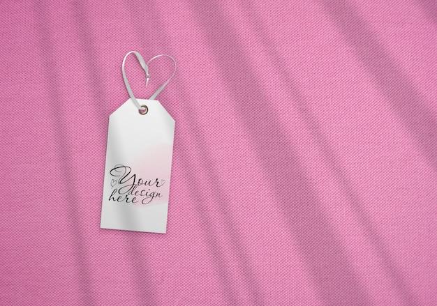 Etykieta bagażowa na tle różowej tkaniny. z cieniami