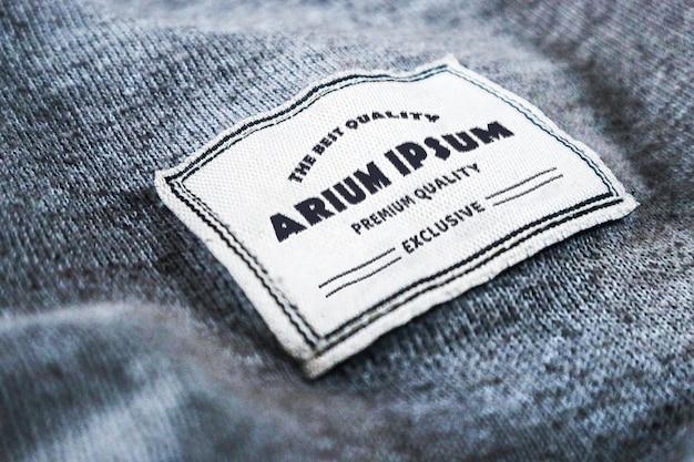 Etykieta z logo makiety wytłoczona na fakturze tkaniny