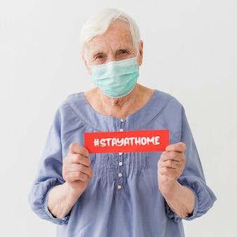 Frontowy widok starsza kobieta z medyczną maskową mienie wiadomością