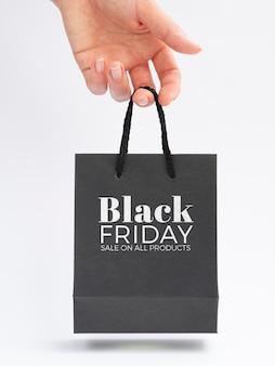 Frontowy widok trzyma czarnego piątek torby pojęcie ręka
