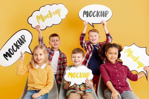 Grupa dzieci trzymających makiety bąbelków czatu
