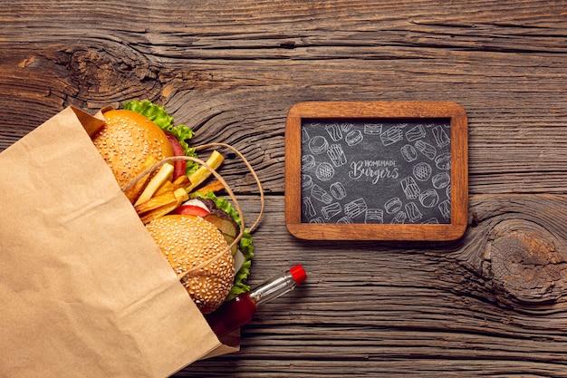 Hamburgeru menu w papierowej torbie na drewnianym tle i ramowym drewnianym tle