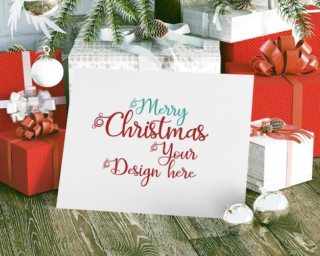 Kartka świąteczna obok pudełek na prezenty świąteczna makieta