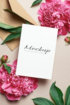 Kartka z życzeniami stacjonarna makieta z kopertą i różowymi kwiatami piwonii