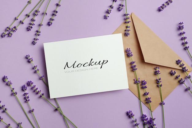 Kartkę z życzeniami lub makieta zaproszenia w kopercie ze świeżymi kwiatami lawendy