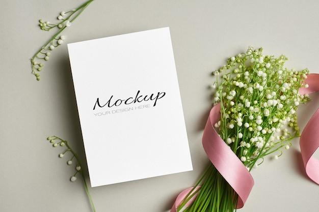 Kartkę z życzeniami lub makieta zaproszenia z bukietem kwiatów konwalii z różową wstążką