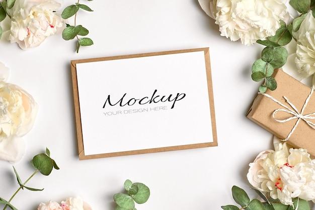 Kartkę z życzeniami lub makieta zaproszenia z kopertą, pudełkiem prezentowym i białymi kwiatami piwonii z gałązkami eukaliptusa