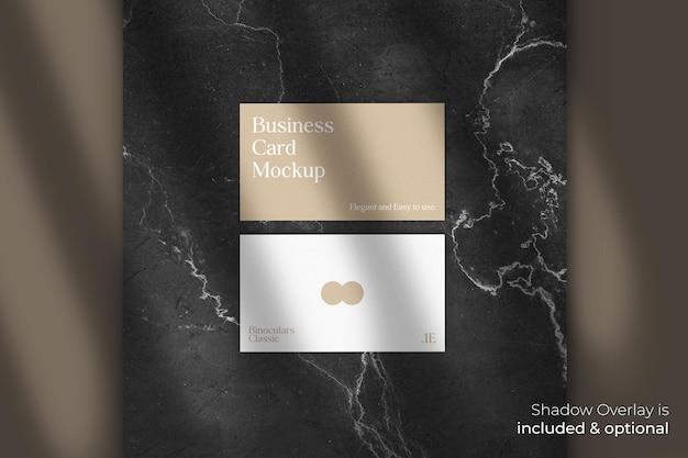 Klasyczna elegancka makieta wizytówki z nakładką cienia na marmurowym kamieniu