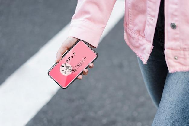 Klient korzystający z aplikacji mobilnej i chodząc po makiecie ulicy