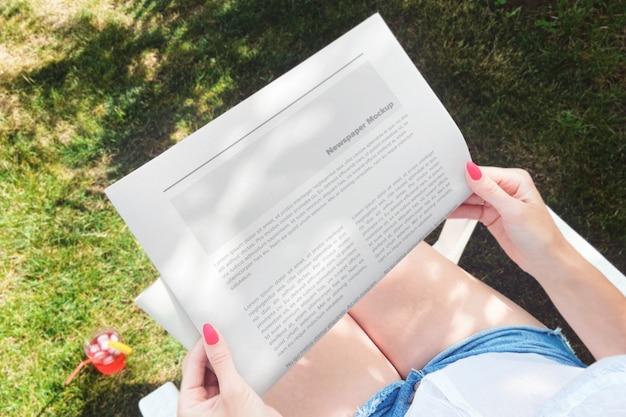 Kobieta czyta gazetę w makiecie podwórka