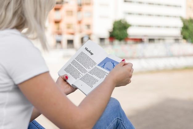 Kobieta czytająca książkę na ulicy z bliska