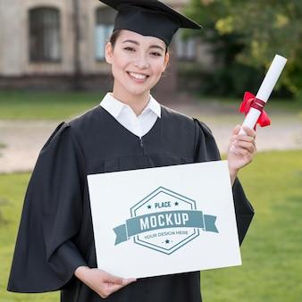 Kobieta dumnie trzymająca makiety dyplomu
