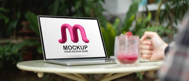 Kobieta freelancer trzyma szklankę napoju na stole z makietą laptopa