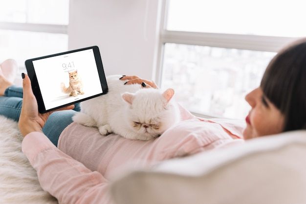 Kobieta na kanapie z kota i tabletu makieta