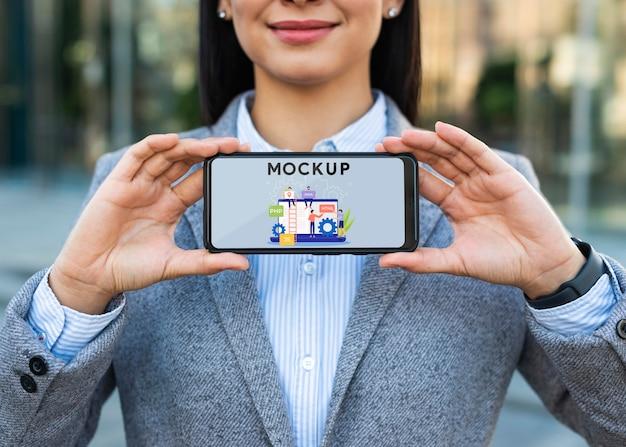 Kobieta na zewnątrz trzymając makietę telefonu