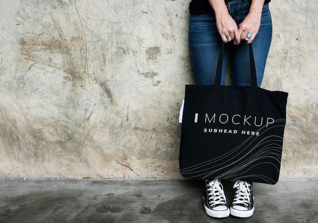 Kobieta niesie czarnego dużego ciężaru torby mockup