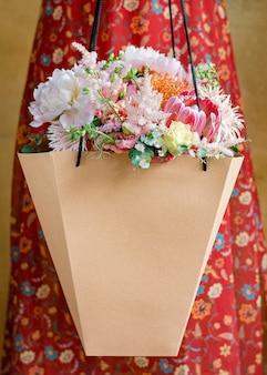 Kobieta niosąca bukiet kwiatów w papierowej torbie