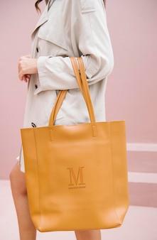 Kobieta niosąca makietę brązowej torebki