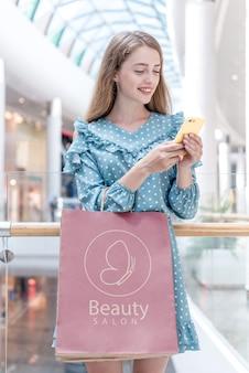 Kobieta patrzeje jej telefon w zakupy centrum handlowym