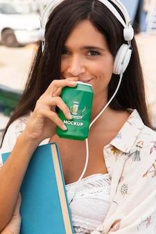 Kobieta pije napoje gazowane i słucha muzyki, trzymając książkę