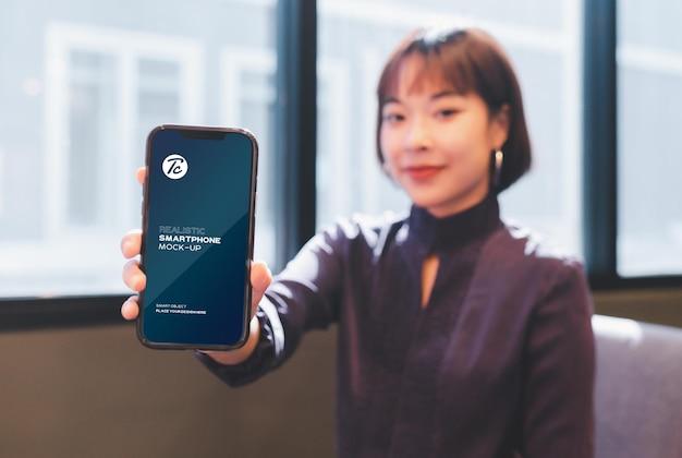 Kobieta pokazuje jej makieta ekranu smartfona w kawiarni.