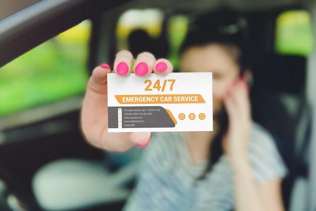 Kobieta pokazuje wizytówkę przez okno samochodu makieta