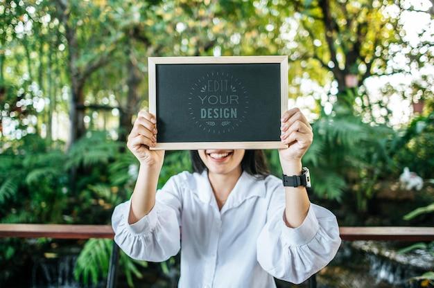 Kobieta ręka trzyma makieta tablicy